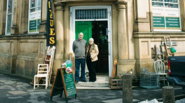 Two people standing outside the Antiques Quarter