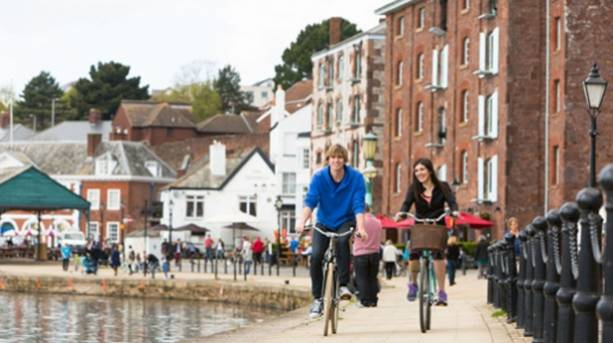 Two people exploring Exeter's quayside by bicycle