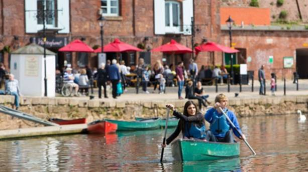 Two people exploring the River Exe by canoe at Exeter's quayside