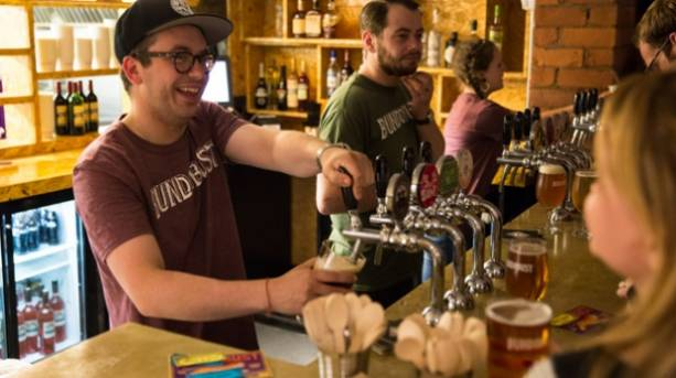 A bartender pulling a pint