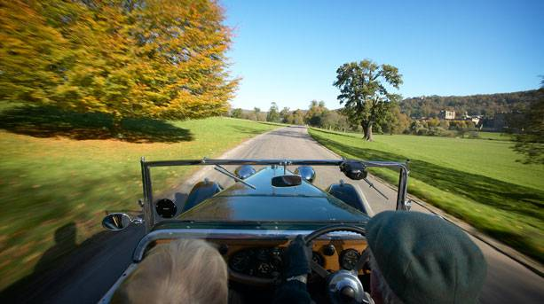 A man and a woman driving an old fashioned 1930's Lagonda classic car