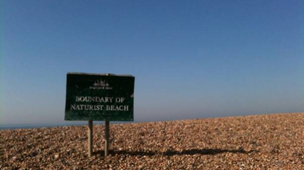 Photo of Brigton Beach with a sign warning people they are about to go on to the nudist part of the beach