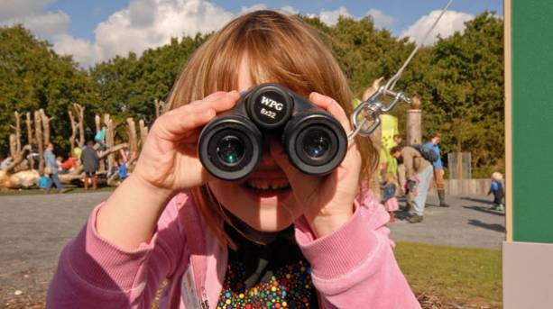 A child looking through binoculars at RSPB-Minsmere