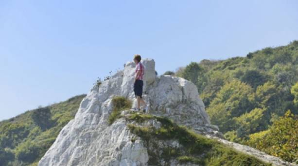 A man a top of a white cliff in Eastbourne