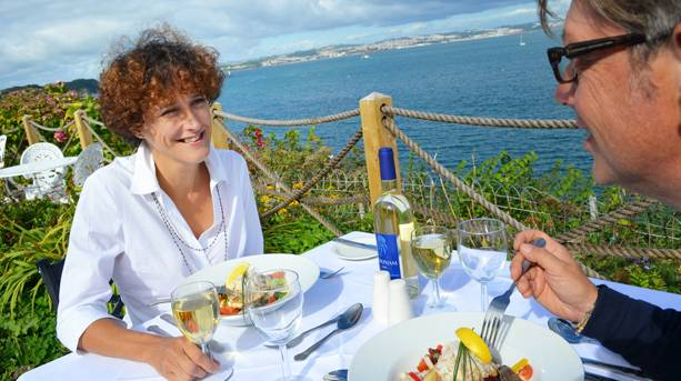 A couple enjoying a meal and the view of the coast