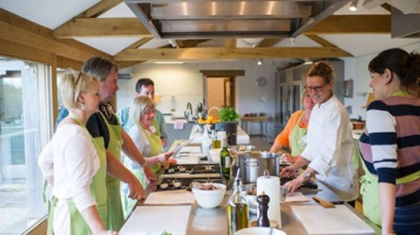 A group of people having a cookery lesson at