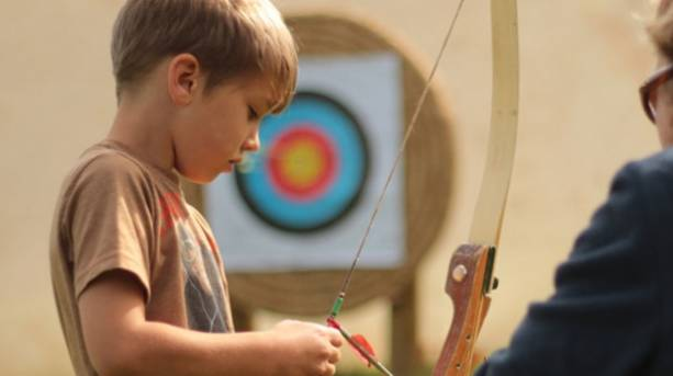 Boy learning archery at Mendip Snowsport Centre