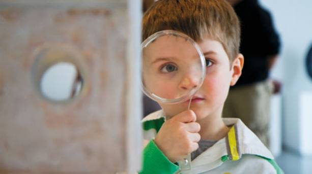 A boy holding a magifying glass to his eye