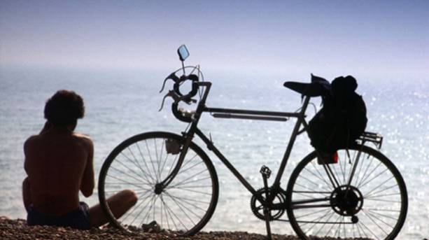 Photo of someone relaxing on the beach next to their bicycle
