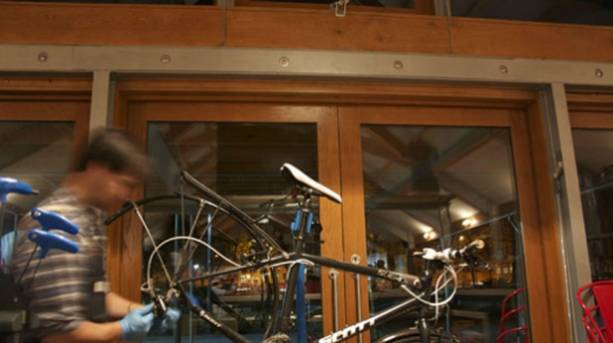 Photo of a man working on a bicycle at the Velo Café