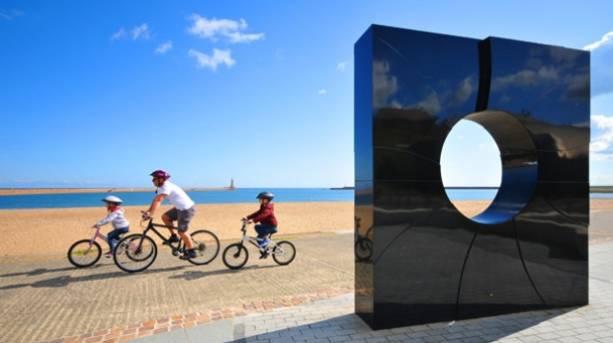 A family cycling on Roker Beach