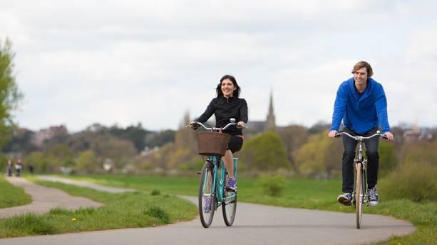 Couple cycling along the river Exe