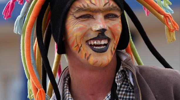 A man with tiger paint face at Sidmouth Folk Week