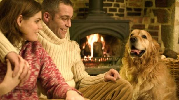 A couple sitting by the fire with their dog in a cottage