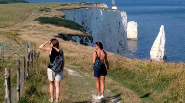 Two women walking towards Old Harry Rocks on a coastal break to Dorset's World Heritage Coast.