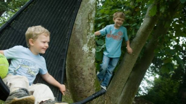 Children playing in the trees at Norburton Hall in Dorset