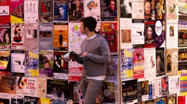 Photo of someone leaning on a poster wall for Fringe events