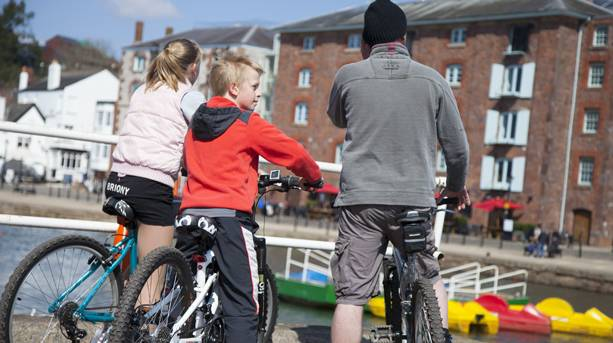 A family cycling along Exeter Quay