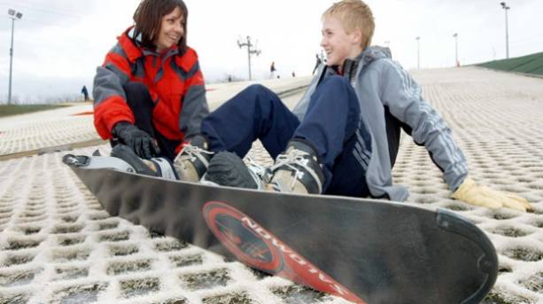 Young boy receiving instruction on snowboarding at Silksworth Ski Slope