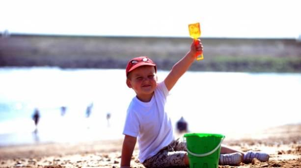 A boy with a bucket and spade on the beach