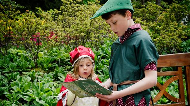 Two kids dressed up in costume reading a story book