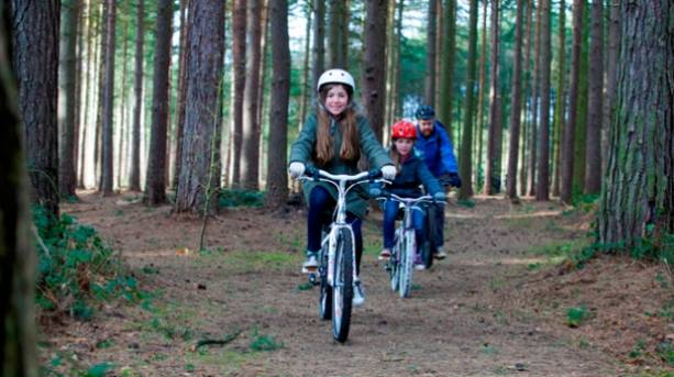 Father and two daughters cycling in Sherwood Pines Forest