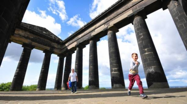 Dad and son walking round the base of Penshaw Monument
