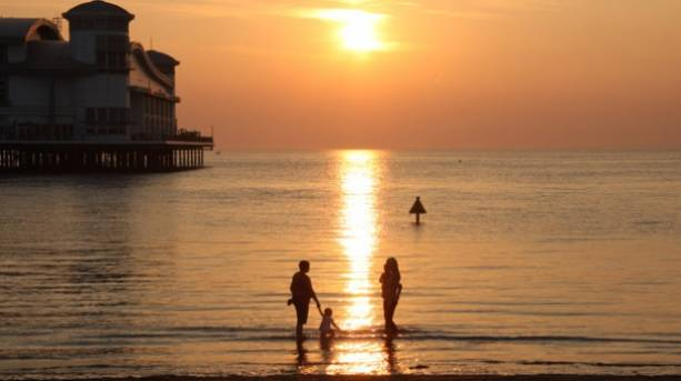 Family paddling near Grand Pier on Weston-super-Mare beach at sunset