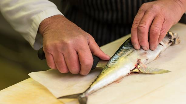 A fishmonger in Norwich Market shows how to fillet an English mackerel
