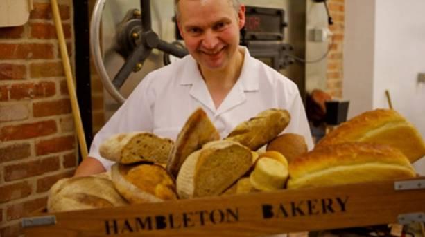 A baker holding a trayful of bread at Hambleton Bakery