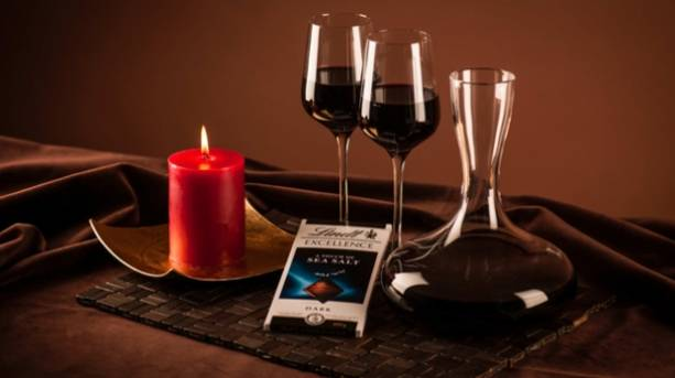 Two glasses of red wine and a bar of sea salt chocolate
