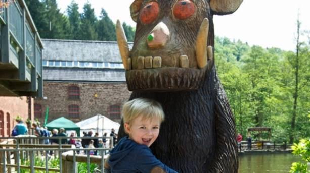 A child hugging a wooden Gruffalo sculpture