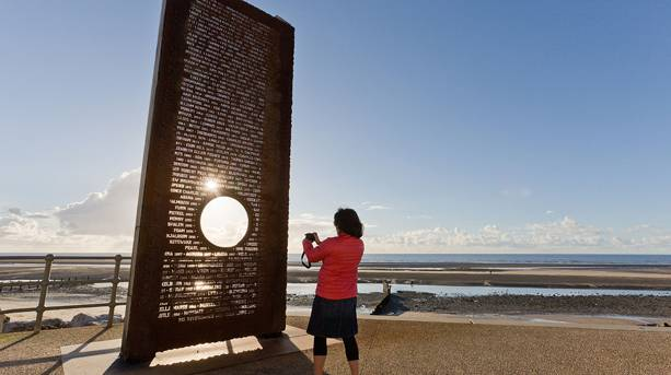 A woman taking pictures on the Mythical Coastline Sculpture Trail, Cleveleys, Lancashire