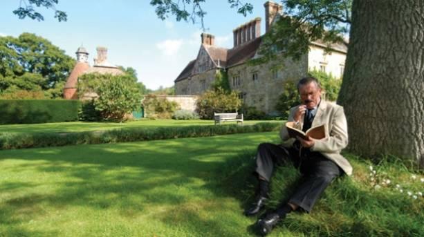 An actor dressed as Rudyard Kipling sitting outside Batemans reading a book