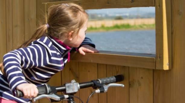 A girl bird watching along the Exe Estuary Trail