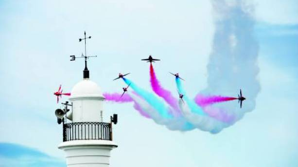 Red Arrows flying over a lighthouse