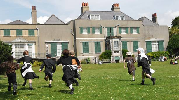 Children in Edwardian clothing running towards the manor