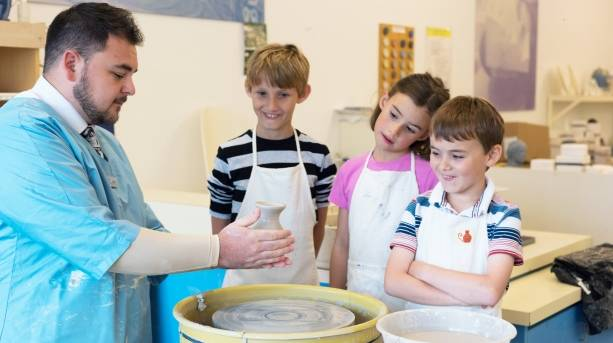 A group of children having a go at making pottery