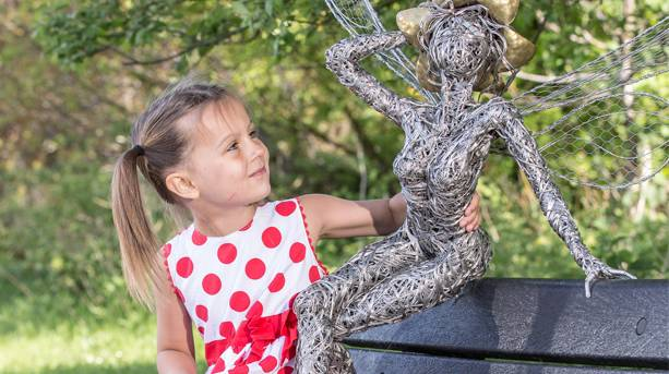 A little girl looking at a fairy scuplture at Trentham