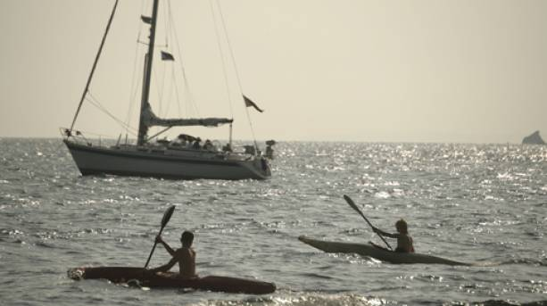 Sea canoeists and a small sailing yachton the Isle of Wight