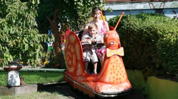 A woman and a child riding on a Joyland Snails ride