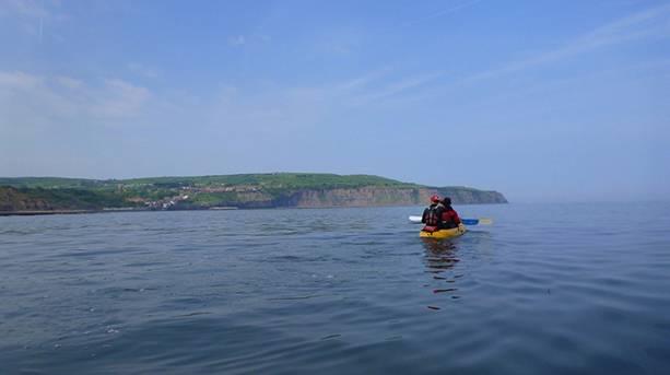 Two people kayaking across Robin Hood's Bay