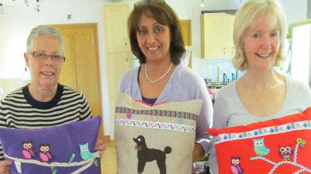 Three ladies holding sewn cushions at Heath House Studios