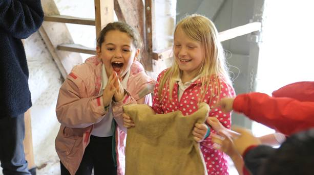 Children learning about the traditional methods of milling