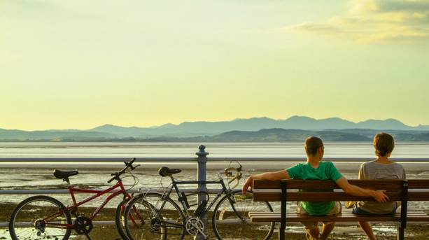 Two cyclists resting on a bench at Morecambe Bay
