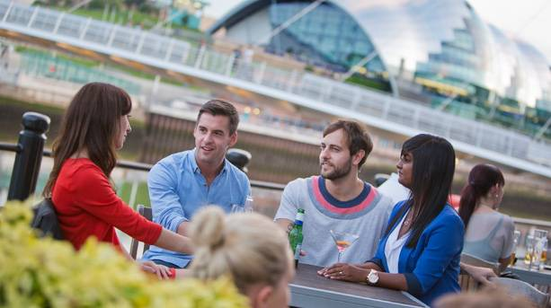 A group of young people enjoy drinks at Newcastle's Quayside