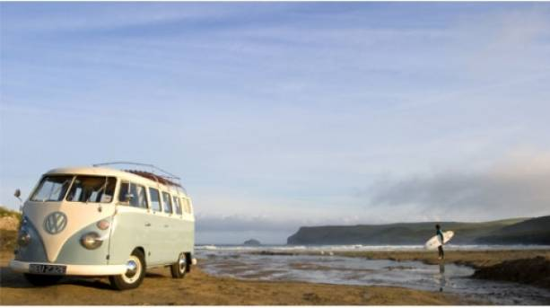 Surfer and camper van on the beach, Polzeath