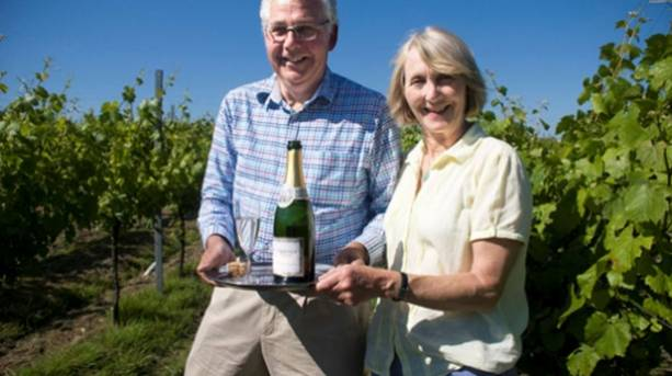 A photo of the owners of Court Garden vineyard with a bottle of their award-winning sparkling wine