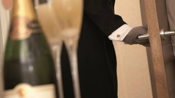 A butler delivering two glasses of Champagne