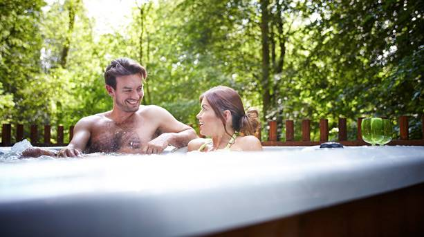 A couple relaxing in an outdoor hot tub in Thrope Forest in Norfolk